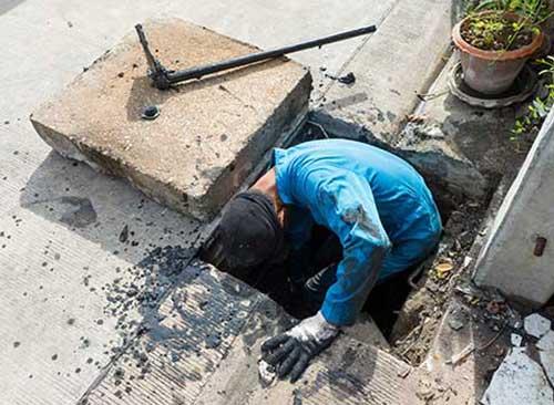 Workman repairing a drain